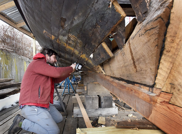 BRYAN EATON/Staff Photo. Mike Brittan, who worked on restoration of the replica of the Mayflower at Mystic Seaport, is now at Lowell's Boat Shop in Amesbury helping to restore the shallop that will be reunited with the mother ship when is makes its appearance in May in Boston Harbor. High school students have also been working on the craft, the original one of which was stored in sections of the Mayflower and when the Pilgrims landed in the New World was reassembled for exploration along the shores looking for a suitable spot for the ship to anchor.