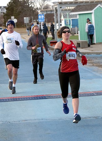 BRYAN EATON/Staff photo. Amy Bernard of Hampstead, N.H. is the first female to cross the finish   in the 5K race in the Hangover Classis at Salisbury Beach.