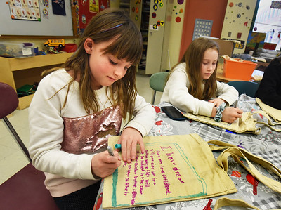 BRYAN EATON/Staff Photo. Students in Newbury Elemtary School's afterschool program Kids Club, decorated tote bags with quotes from Marting Luther King Jr., like Olivia Strand, 8, left, and Addie France, 9. The project is for a Triton School District-wide MLK Day of Caring with students from Salisbury Elementary School collecting toiletries and the Pine Grove School collecting books which will fill the totes to be given to Pettengill House and other service organizations.
