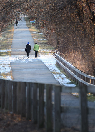 BRYAN EATON/Staff Photo. Walkers along the Great Eastern Marsh Trail off Mudnock Road in Salisbury walk through a late afternoon ray of sun on Thursday afternoon. The sun will be scarce throughout the weekend as rain is in the forecast for Saturday with some snow possible on Sunday morning.