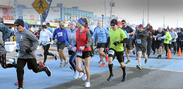 BRYAN EATON/Staff photo. Runners in the 10K race of the Hangover Classic at Salisbury Beach start out from the beach center.