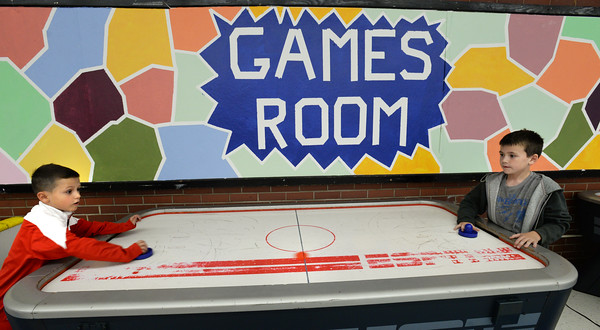 BRYAN EATON/Staff photo. Jack Ferreira, 8, left and Jason Raymond, 7, both of Salisbury play a game of air hockey Thursday afternoon. They were in, yes, the games room at the Boys and Girls Club