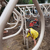 Newburyport: Chad White of CMJ Construction of Bangor, Maine tamps down the bottom of supports for monkey bars, later pouring in concrete, in the new Brown School Playground. His company is constructing the equipment made by Gametime. Bryan Eaton/Staff Photo