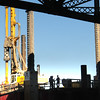 BRYAN EATON/ Staff Photo. Workers on the new Whittier Bridge project are silhouetted on pilings which will hold cranes that will construct the south bound lane side of the bridge, once the northbound lane is open, in a view taken aboard a boat on Thursday morning.