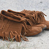JIM VAIKNORAS/Staff photo Two pair of moccasin sit on the beach at the annual Inter-Tribal Pow Wow at Plug Pond in Haverhill Saturday.