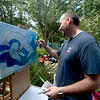 JIM VAIKNORAS/Staff photo Illustrator Matt Tames of Exeter paints a pair of playful whales at the 92.5 Riverfront Festival in Market Landing Park in Newburyport Saturday.