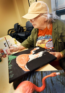 BRYAN EATON/Staff photo. Nancy Berube puts in some green leaves on a painting of a pink flamingo in an acrylics class taught by Suzanne Speede at the Amesbury Senior Center on Wednesday morning. The Amesbury resident, who retired three years ago, started to dabble in painting and joined the classes to get better at it.