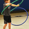 BRYAN EATON/Staff photo. Kevin Marshall, 5, and his fellow kindergartners used hula hoops in Margaret Welch's physical education class at Amesbury Elementary School on Thursday. In addition to using them as they're intended, they also did some stretching excercises with them, here, and rolled them along trying to keep them from falling over.