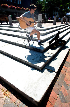 JIM VAIKNORAS/Staff photo Anthony Lupetri casts a shadow as he plays guitar on Inn Street in Newburyport Monday morning. Anthony lives in Seabrook and is a student at Winnacunnet High School.