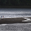 BRYAN EATON/Staff photo. Two people with their boat check out the sandbar in the Merrimack River on the Amesbury and Merrimac town line on Thursday. They may have made a quick trip back to shore after this photo was taken as lightning came through the area.