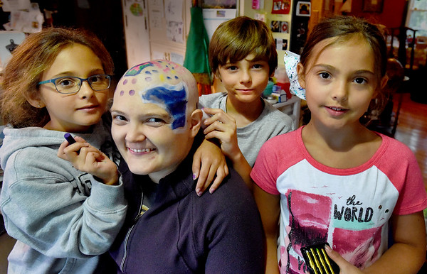 BRYAN EATON/Staff photo. Amesbury resident Erin Hutchinson-Himmel, who's going in for another round of chemotherapy, got her head decorated by her children, triplets, from left, Sophie Himmel, Charlie and Maggie.