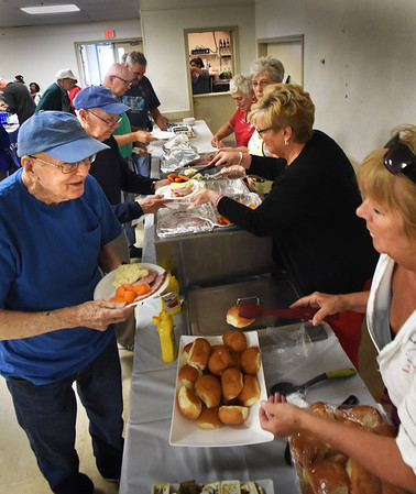 BRYAN EATON/Staff photo. Veterans line up as volunteers served them baked ham, mashed potatoes and vegetables at the Elks Lodge 909 of Newburyport on Friday in honor of POW/MIA Recognition Day. The luncheon was sponsored by the Elks and the local chapter of Disabled  American Veterans.