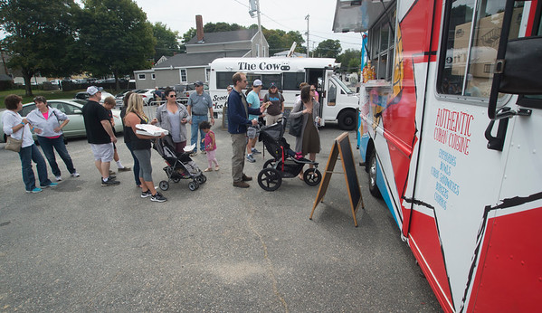 JIM VAIKNORAS/Staff photo Food lovers wait in line for Cuban food at teh Food Truck Festival Saturday at Cashman Park in Newburyport. The event was sponsored my Our Neighbor's Table