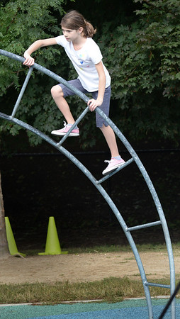 BRYAN EATON/Staff photo. Rebecca Cabral-Silvero climgs the ascending monkey bars at the playground at the Bresnahan School on Wednesday morning. While she and her classmates had indoor recess on Tuesday due to the rain, yesterday was especially nice as it was 80 degrees.