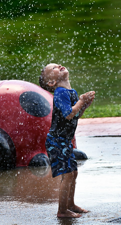 BRYAN EATON/Staff photo. Lucas Roberts, 5, of Haverhill, at Amesbury Town Park with his mother, Maegin, on Thursday afternoon, gets sprinkled at the water park before water fell from the sky two hours later with claps of thunder. The weekend is forecast to be drier and cooler than the past two days.