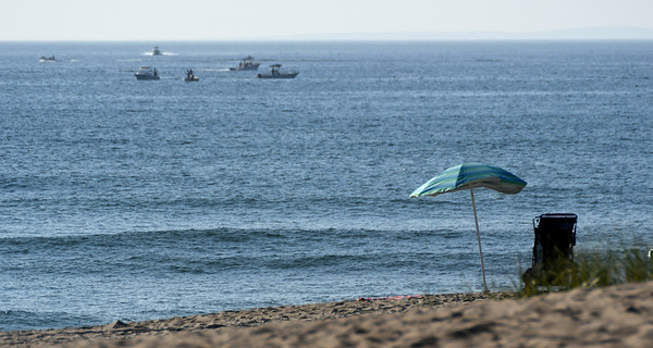 JIM VAIKNORAS/Staff photo A group of boats fish Monday morning in the general vicinity of where a hang glider was reported to have gone down off Seabrook Beach Sunday night.
