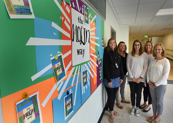 BRYAN EATON/Staff photo. Several of the PBIS team gather at the Molin Way poster, from left, Jesssica Burke; Tara Rossi, principal; Stefanie Berger; Kristin Smolski and Alissa  Gallegos.