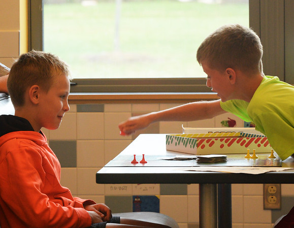 BRYAN EATON/Staff photo. Owen Rouba, 8, looks on as Camden Bates, 7, gets in a good move in the game Sorry at the Bresnahan School on Wednesday afternoon. They were in the YWCA Afterschool program which started last week and goes from school dismissal until 6:00 p.m.