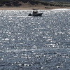 BRYAN EATON/Staff photo. A small fishiing boat heads past the old US Coast Guard station on the Merrimack RIver off Plum Island Point on Thursday afternoon the water sparkling from the back-lit sunlight.