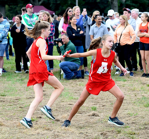 JIM VAIKNORAS/Staff photo Amesbury's Julia Penny hands the baton to Callista Chabot at the Clipper Relay at Maudslay State Park Saturday.