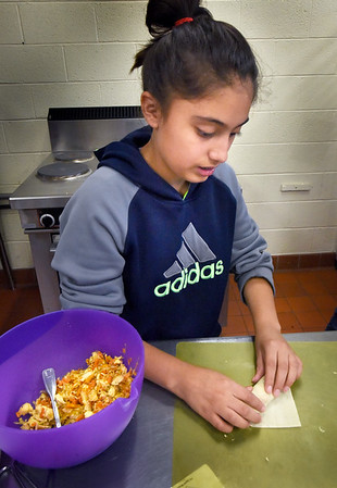 BRYAN EATON/Staff photo. Gabby Galarza, 12, tries her hand at making vegetable chicken egg rolls in Cooking With Carol which resumed last week at the Boys and Girls Club in Salisbury. Teacher Carol Chiungos had the children making healthy lunches which included the egg rolls, which were baked, vegetable and chicken wraps, fruit salad and low-fat oatmeal cookies.