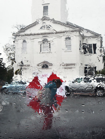 BRYAN EATON/Staff photo. A person with an umbrella walks down Pleasant Street across from the Untiarian Church in Newburyport as rain on a windshield blurs the scene. Rain is still possible later today with temlperatures close to 80 degrees.
