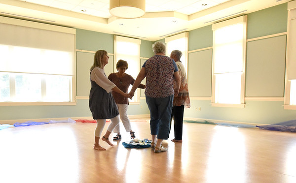 """BRYAN EATON/Staff photo. Dance instructor Ellen Kennedy, left, leads people in dance, with more joining when the camera was put away, at the Newburyport Senior Center. Her """"Sacred Circle Tradition"""" helps to increase balance, flexibility and relaxation."""