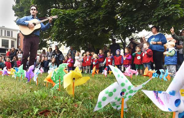 """BRYAN EATON/Staff photo. In the midst of pinwheels arranged in the shape of the peace symbol, Newburyport Montessori School music teacher Neal Ferreira leads students in the song """"Light a Candle For Peace"""" on Friday morning. The school was observing International Day of Peace which is celebrated around the world with the U.N. General Assembly declaring September 21 """"as a day devoted to strengthening the ideals of peace, both within and among all nations and peoples."""""""