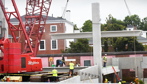 BRYAN EATON/Staff photo. A huge crane lowers a piece of decking for the new parking garage being built in downtown Newburyport on Monday morning. Titcomb Street is closed to traffic as the flatbed trucks bringing the giant pieces use the street to unload the cargo.