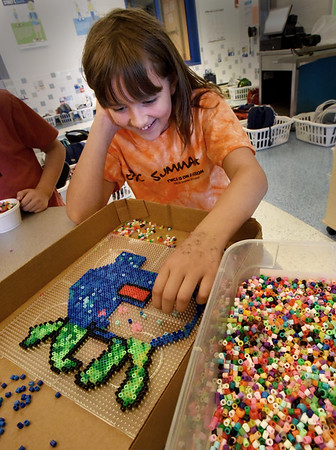 BRYAN EATON/Staff photo. Victoria Rogers, 9, creates a Pokemon character during a fusion bead project at the YWCA Afterschool Program at Newburyport's Bresnahan School. She's creating the image freehand, and when it's done will move a warm iron over to melt the beads into a permanent piece of art.