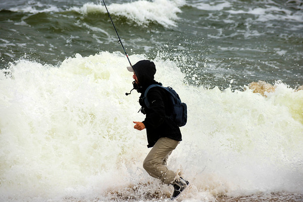 JIM VAIKNORAS/Staff photo Matt Shea of Plastow NH, gets hit by a wave while surf casting at Salisbury Beach Reservation Friday afternoon.