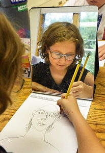 BRYAN EATON/Staff photo. Sydney Richards, 9, draws a self-portrait in Sara Ramos' art class at the Amesbury Elementary School. The project is part of Square 1 Art is a fundraiser through the school's PTO where parents can have their children's artwork put on t-shirts, mugs, etc.