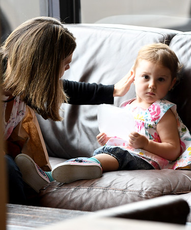 JIM VAIKNORAS/Staff photo Angelica Wilkofski of Bradford brushes the hair of her daughter Isabel, 2, as they sit in the window seats at Commune Cafe on Pleasant Street in Newburyport Friday.
