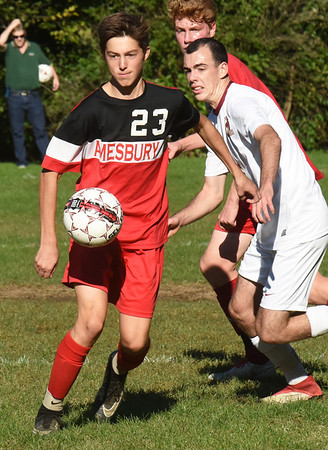 BRYAN EATON/Staff photo. Amesbury's #23 and Ronan Harrington go for the ball.