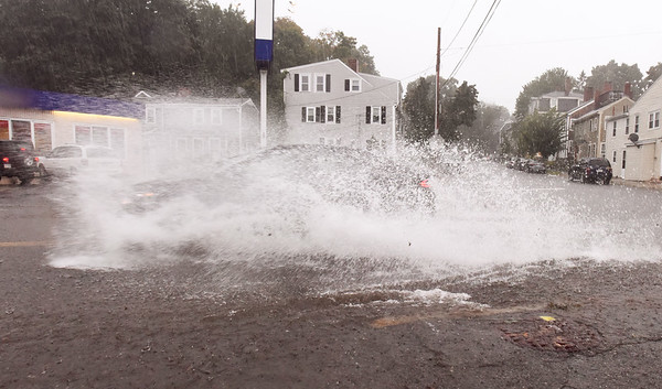 BRYAN EATON/Staff photo. A car riding through a puddle at the bottom of Kent Street at Merrimac Street in Newburyport was hidden by the spray it created at the height of Tuesday's rain, the remnants of Hurricane Florence. One person is Salisbury measured five inches of rain in a tub that was left out overnight.