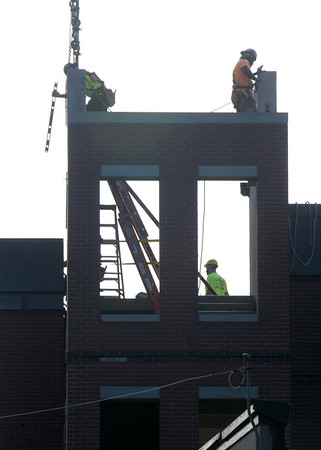 BRYAN EATON/Staff photo. A construction crew is silhouetted on a recent morning by a hazy sun working in one of the stairwells at the new parking garage in downtown Newburyport. Much of the facade has gone up on the northwest side and more deck units were seen being delivered Monday morning.