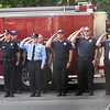 BRYAN EATON/Staff Photo. Newburyport Fire Department Chief Christopher LeClaire, right, along with firefighters and police officers salute at the flag is lowered to half staff during 9/11 remembrance at the station Wednesday morning.