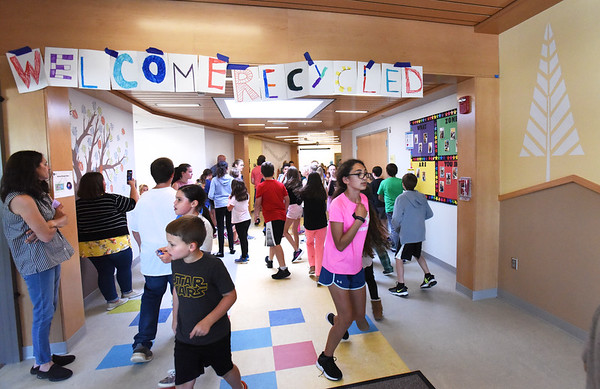 BRYAN EATON/Staff photo. Students at the Pine Grove School in Rowley scramble through the new lobby in search of Easter Eggs. The band Recycled Percussion and program Chaos and Kindness were at the school getting students involved in the act with music and fun at an assembly after.