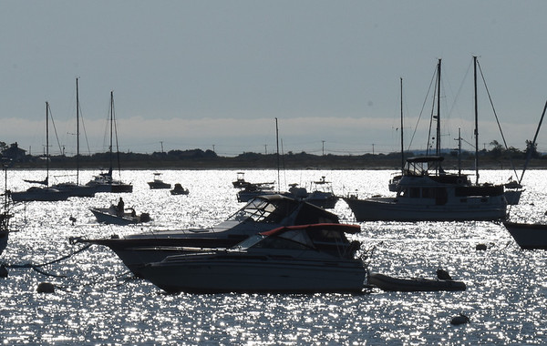 BRYAN EATON/Staff Photo. A boater, right, passes many more boats moored in Newburyport Harbor, the sun reflecing on the Merrimack River. The rest of the week and into the weekend look ideal for outdoor activities.