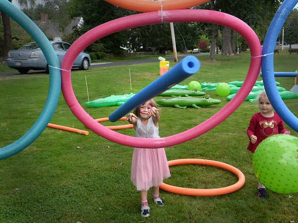 BRYAN EATON/Staff photo. Willa Hendrick, 3, of Newbury tossed a noodle though some hoops at Newbury's Upper Green on Saturday. She was attending the Good Vibes Festival which was a fundraiser for the Community Food Pantry at the First Parish Church of Newbury.
