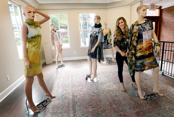 "BRYAN EATON/Staff Photo. Newburyport Art Association executive director Jessica Pappathan stands among mannequins wearing dresses from the ""The Day Art Met Fashion"" show from last week. Members created different pieces that were used on the dresses by a company in Canada and facilitated by the Elephant's Trunk on Inn Street where items can be ordered. Some of the proceeds will be donated to the art association."