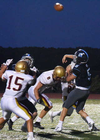 BRYAN EATON/Staff photo. Triton quarterback Kyle Odoy gets off a pass as Newburyport defenders rush in.