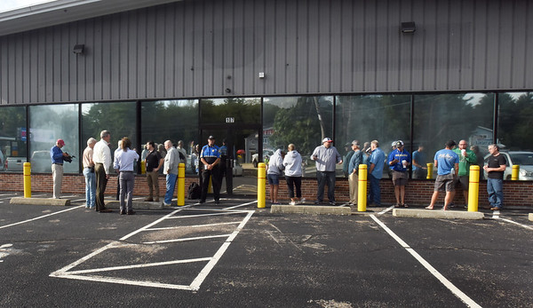 BRYAN EATON/Staff Photo. Salisbury town officials at left, and customers await the opening of Alternative Therapies Group, which sells marijuana-related products, on Wednesday morning.