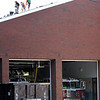 BRYAN EATON/Staff Photo. Roofers work to scrape off the shingles to be replaced at the Newburyport Fire Station on Greenleaf Street on Tuesday morning. The headquarters, opened in 1978, replaced the fire station that was in the Firehouse Center for the Performing Arts in Market Square, which, before it was a fire station, housed a market.