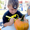 BRYAN EATON/Staff photo. A pirate and Batman afficianado, Sam Foss, 7, of Salisbury decorates a pumpkin at a booth sponsored by the Institution For Savings.