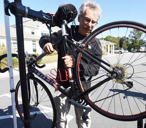 BRYAN EATON/Staff photo. Newburyport resident Jim Goldberg of Easy Rider Tours helps Pedalin' Fools mobile bike services of Plaistow, N. H. at the Repair Cafe at the Newburyport Senior and Community Center on Saturday. The event, the fourth, was sponsored by Time Trade of Greater Newburyport and Toward Zero Waste of Newburyport which fosters repairing things that can be salvaged instead of discarded into the waste stream.