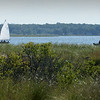 BRYAN EATON/Staff Photo. A sailboat catches an onshore breeze just off Salisbury Beach State Reservation as it heads up the Merrimack River on Tuesday afternoon. There were noticeably less campers and beach-goers now that the unofficial end of summer passed on Labor Day.