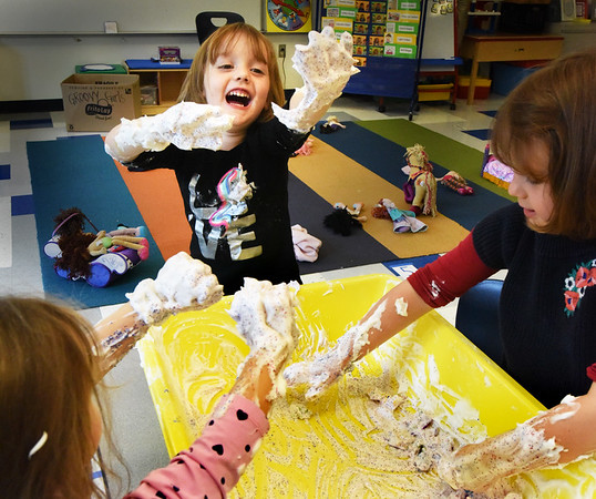 """BRYAN EATON/Staff Photo. MkKenna Farnell, 4, exclaims """"this is the best day of my life"""" as she and Hannah DeSimone, left, and Emily Fortmann, right, both 4, mix their hands in shaving cream with glitter being sprinkled on them. They were in Tanahi Fahey's full day pre-kindergarten class where the youngster were learning about the five senses, here using all but taste in there """"hands on"""" learning experience."""