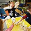 "BRYAN EATON/Staff Photo. MkKenna Farnell, 4, exclaims ""this is the best day of my life"" as she and Hannah DeSimone, left, and Emily Fortmann, right, both 4, mix their hands in shaving cream with glitter being sprinkled on them. They were in Tanahi Fahey's full day pre-kindergarten class where the youngster were learning about the five senses, here using all but taste in there ""hands on"" learning experience."