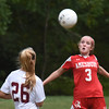 BRYAN EATON/Staff Photo. Amesbury's Meghan McElaney readies to head the ball as Matigan DeFeo moves in.